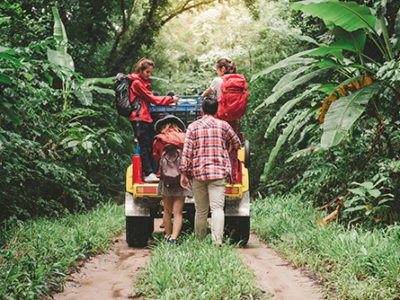Happy asian young travellers with 4WD drive car off road in forest, young couple walking with backpacks and another two are enjoying on 4WD drive car. Young mixed race Asian woman and man.